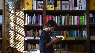 Un homme lit un livre dans une librairie, à Porto, le 12 janvier. (MIGUEL RIOPA / AFP)