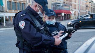 Des policiers effectuent un contrôle des attestations de respect du couvre-feu à Montauban (Tarn-et-Garonne), le 19 février 2021. (PATRICIA HUCHOT-BOISSIER / HANS LUCAS / AFP)