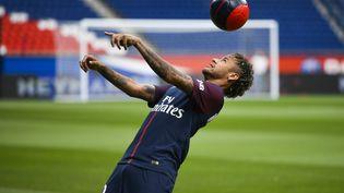 Neymar jongle avec un ballon, le 4 août 2017, lors de sa présentation officielle au Parc des princes, à Paris. (LIONEL BONAVENTURE / AFP)