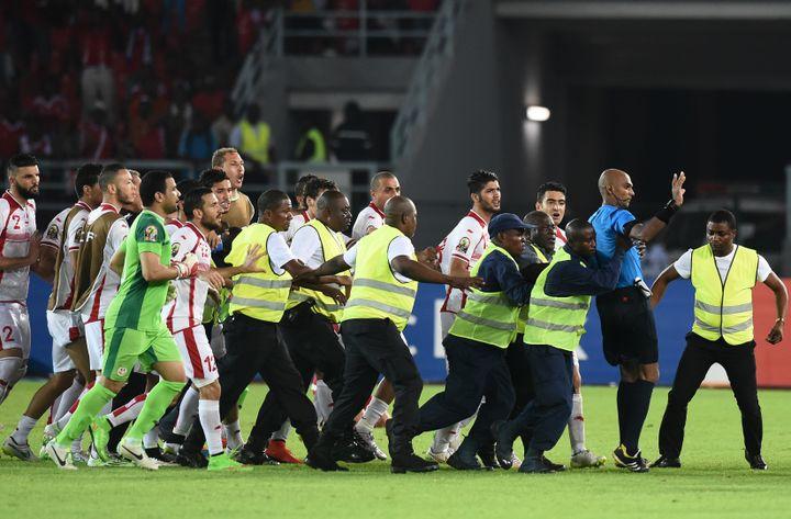 Les stadiers protègent l'arbitre du match Guinée équatoriale-Tunisie de la colère des joueurs tunisiens, le 31 janvier 2015, à Bata (Guinée équatoriale). (CARL DE SOUZA / AFP)