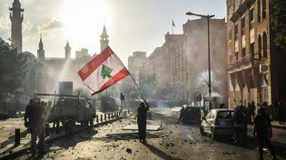 Un manifestant porte un drapeau du Liban à Beyrouth, le 9 août 2020. (NURPHOTO/AFP)
