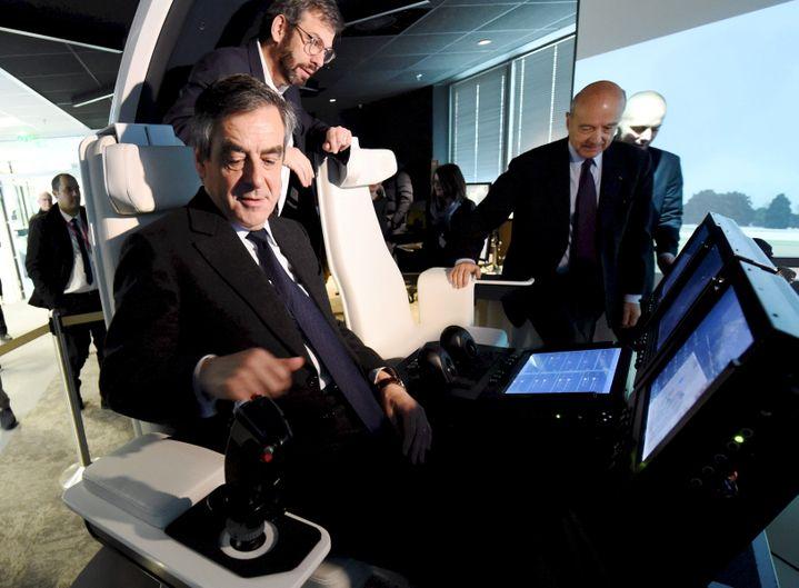 François Fillon et Alain Juppé prennent place à bord d'un simulateur d'hélicoptère, à l'usine Thales de Mérignac (Gironde), le 25 janvier 2017. (MEHDI FEDOUACH / REA)