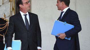Le président François Hollande en discussion avec le Premier ministre Manuel Valls à la sortie du Conseil des ministres, le 19 août 2015. (STEPHANE DE SAKUTIN / AFP)