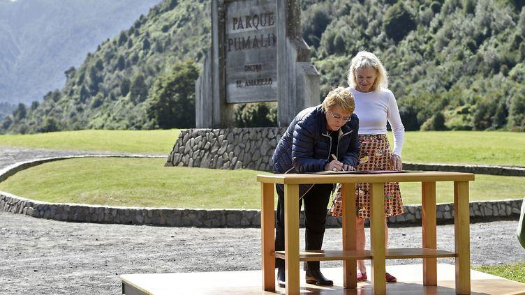 La présidente chilienne, Michelle Bachelet, signe un document sur une donation de terres aux côtés de la veuve de Douglas Tompkins, Kristine McDivitt, le 15 mars 2017, à Parque Pumalin (Chili). (PRESIDENCIA DE CHILE / AFP)