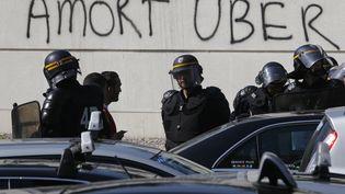 Des policiers lors des affrontements entre conducteurs de VTC et taxis en grève, à Paris, le 25 juin 2015. ( CHARLES PLATIAU / REUTERS)