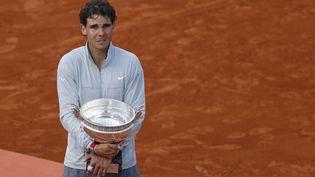 Rafael Nadal verse des larmes de joie sur le cour central de Roland Garros (Paris), après avoir remporté son neuvième titre face à Novak Djokovic, le 8 juin 2014. (PATRICK KOVARIK / AFP)
