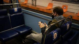 Un homme consulte son téléphone portable dans le métro, à Paris, le 8 mai 2020. (LAURE BOYER / HANS LUCAS / AFP)