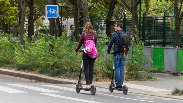 Deux personnes utilisentdes trottinettes électriques, le 30 septembre 2018 à Paris. (RICCARDO MILANI / HANS LUCAS / AFP)