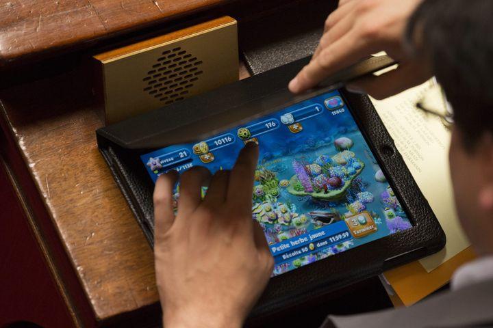 Un député en pleine séance de jeu sur sa tablette, lors des questions au gouvernement du 19 juin 2013. (  MAXPPP)