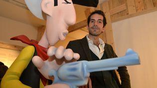 Le nouveau scénariste de la série Lucky Luke pose à côté du célèbre cow-boy solitaire le 28 janvier 2016 à Angoulême. (GEORGES GOBET / AFP)