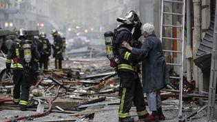 Un pompier vient en aide à une femme rue de Trévise, le 12 janvier 2018. (THOMAS SAMSON / AFP)