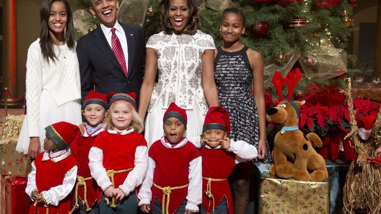 Le président américain Barack Obama, entouré de son épouse Michelle et de leurs filles Sasha et Malia, lors d'une célébration de Noël dans un hôpital de Washington (Etats-Unis), le 15 décembre 2013. (SAUL LOEB / AFP)