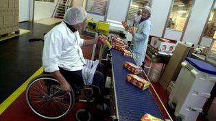 Une personne handicapée travaille sur une chaîne de production dans une entreprise à Houlgate (Calvados). (MYCHELE DANIAU / AFP)