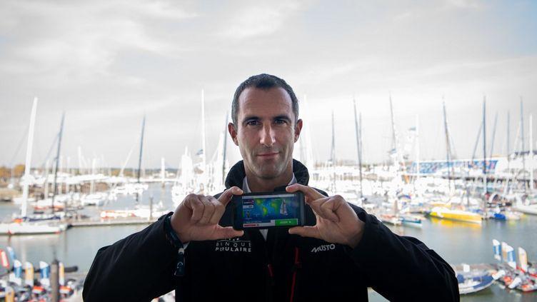 Le skipper français Armel Le Cleac'h montrant le jeu de voile en ligne Virtual Regatta sur son smartphone le 6 novembre 2020; auxSables-d'Olonne. (LOIC VENANCE / AFP)