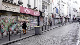 Des piétons passent devant des magasins fermés à Paris, le 15 mars 2020 (photo d'illustration). (STEFANO RELLANDINI / AFP)
