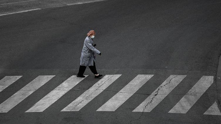 Une femme portant un masque traverse une rue déserte à Paris, le 20 avril 2020. (PHILIPPE LOPEZ / AFP)