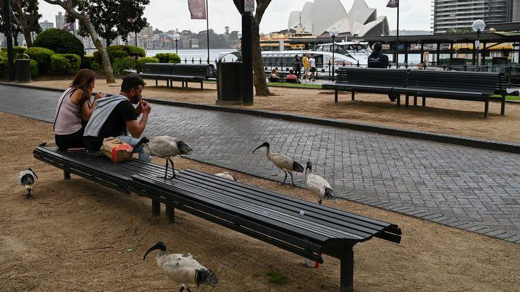 Des Australiens déjeunent sur un banc, à Sydney, le 10 août 2021. (STEVEN SAPHORE / AFP)
