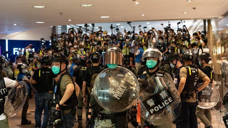 Des policiers face à des manifestants pro démocratie, à Hong Kong, le 10 mai 2020. (YAT KAI YEUNG / NURPHOTO / AFP)