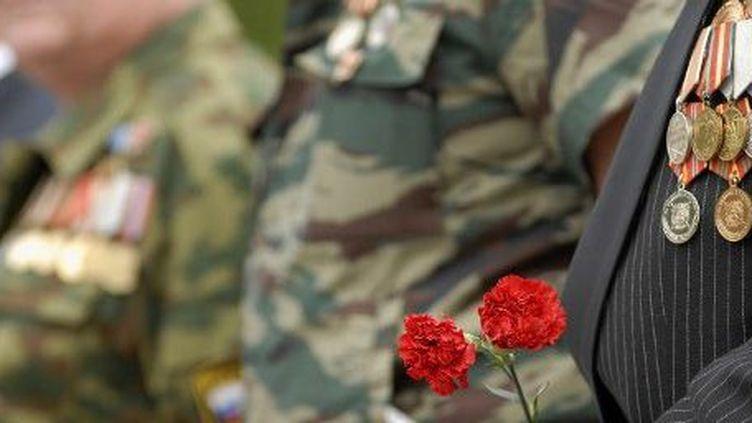 A Stavropol (Caucase), un vétéran de l'Armée rouge tient des fleurs devant un monument à la mémoire de militaires soviétiques morts pendant la première guerre d'Afghanistan (1979-1989), à l'occasion du 20e anniversaire de la fin de ce conflit. (AFP - DANIL SEMYONOV)