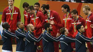 Les joueurs de l'équipe de France de handball saluent les joueurs danois, vainqueurs de la finale olympique, à Rio de Janeiro (Brésil), le 21 août 2016. (ROBERTO SCHMIDT / AFP)
