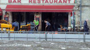 Des restaurateurs nettoient leur devanture àQuimperle 'Finistère) après le passage de la tempe Dirk - 25 décembre 2013 (FRED TANNEAU / AFP)