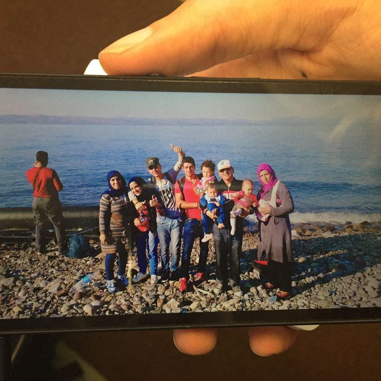La famille Ashour pose sur une plage de l'île de Lesbos (Grèce), en août 2015. Majd est à gauche, de dos, Msalam est au centre, le pouce levé, Wissa à sa droite. (THOMAS BAIETTO / FRANCETV INFO)
