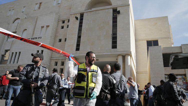 Une secouriste et un agent de sécurité israéliens, le 18 novembre, devant la synagogue attaquée par deux terroristes palestiniens, faisant cinq morts. (JACK GUEZ / AFP)
