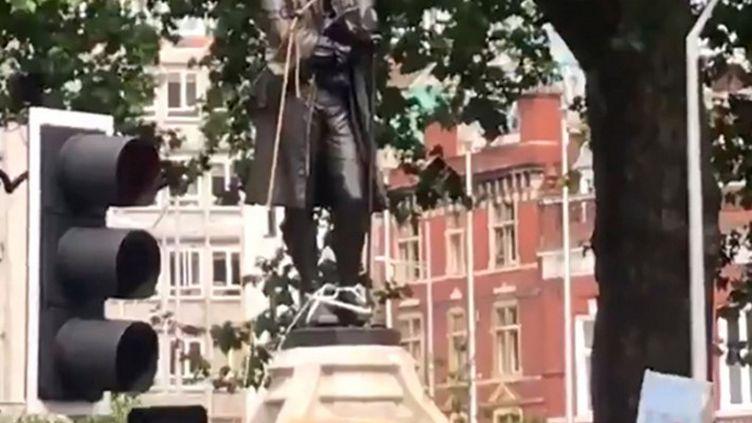 Une capture d'écran d'une vidéo diffusée sur le compte Twitter deWilliam Want (@willwantwrites)qui montre la statue d'Edward Colston en train d'être déboulonnée à Bristol (Royaume-Uni), le 7 juin 2020. (WILLIAM WANT / TWITTER / AFP)