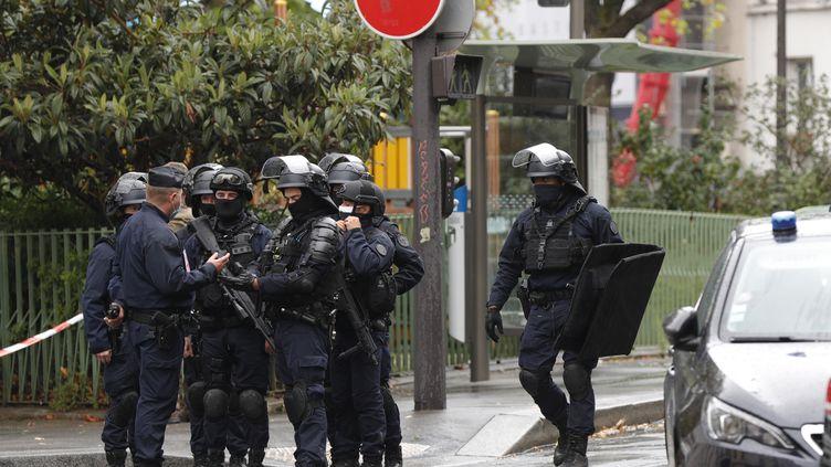 Un groupe de policiers reçoit des instructions sur les lieux de l'attaque à l'arme blanche qui a visé des salariés de Premières Lignes, dans le 11e arrondissement de Paris, le vendredi 25 septembre. (GEOFFROY VAN DER HASSELT / AFP)
