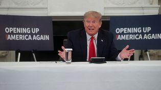 """Le président Donald Trump lors d'une réunion avec les chefs d'industrie américains à la Maison Blanche, devant des panneaux """"Rouvrir l'Amérique"""", le 29 mai 2020. (JONATHAN ERNST / X90178)"""
