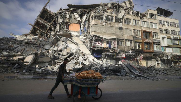 Un homme passe devantun bâtiment détruit par des frappes israéliennes, dans la ville de Gaza, le 20 mai 2021. (MAHMUD HAMS / AFP)