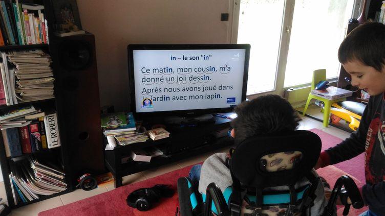 Antoine, 14 ans, et Arthur, 10 ans, devant la télévision durant la période de confinement, le 25 mars à Meylan (Isère). (SERVANE HUGUES)