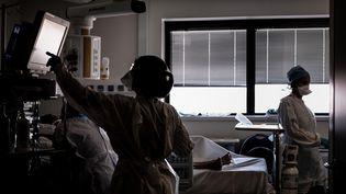 Des soignants dans la chambre d'un patient du Covid-19, dans le service de réanimation de l'hôpital de La Croix-Rousse, à Lyon (Rhône) le 15 septembre 2020 (JEFF PACHOUD / AFP)