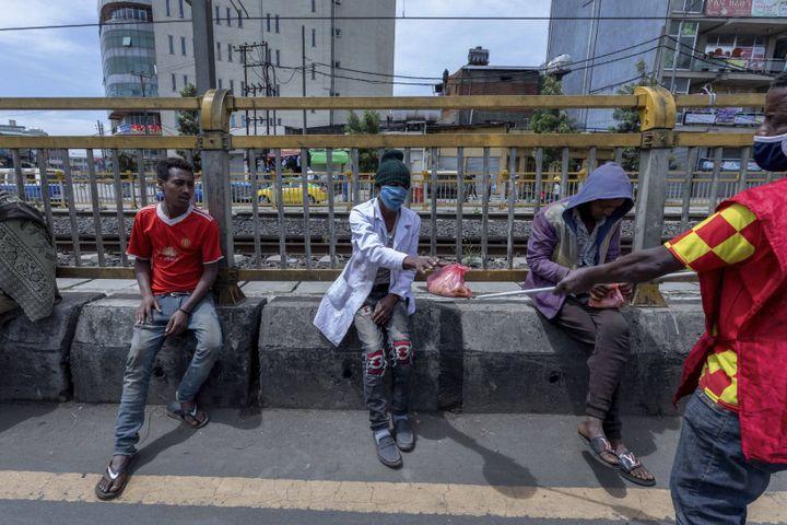 Distribution de repas à des sans-abri à Addis Abeba le 19 avril 2020. Les volontaires utilisent une perche métallique pour leur tendre la nourriture etéviter ainsi le risque de répandre le coronavirus. (MULUGETA AYENE/AP/SIPA / SIPA)