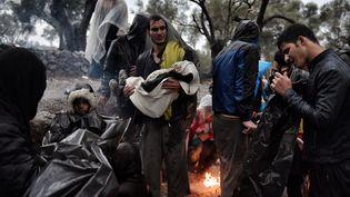 Migrants sous la pluie à Lesbos en 2015  (Aris MESSINIS / AFP)