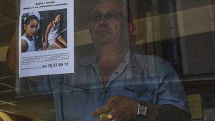 Le propriétaire d'un bar dePont-de-Beauvoisin (Isère) affiche l'appel à témoin lancé pour retrouverMaëlys, lundi 28 août 2017. (PHILIPPE DESMAZES / AFP)