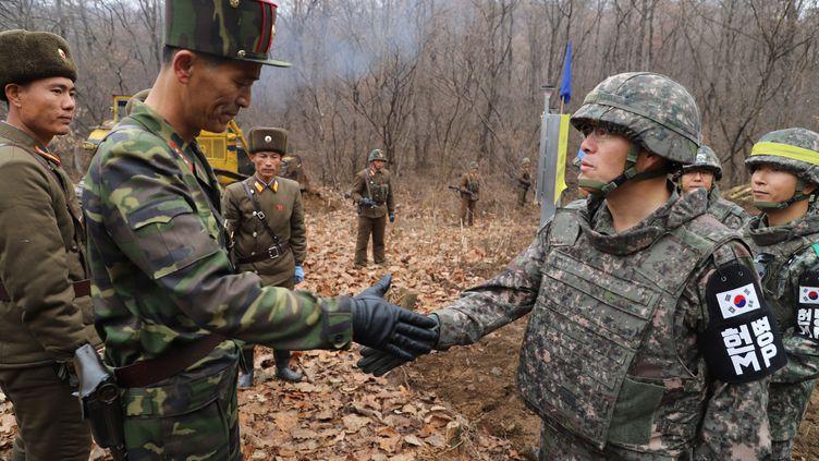 Deux militaires représentant les deux Corées sont sur le point de se serrer la main, le 22 novembre 2018, sur la frontière, dansla Zone démilitarisée. (SOUTH KOREAN DEFENCE MINISTRY / AFP)