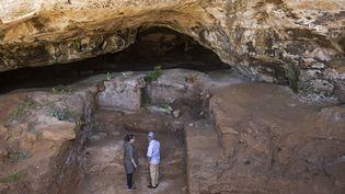 Des archéologues devant l'entrée de la grotte des Contrebandiers, près de Rabat au Maroc, le 18 septembre 2021. (FADEL SENNA / AFP)