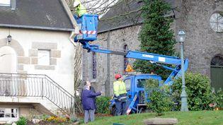 Des employés d'ERDF réparent une installation électrique à Saint-Brieuc (Côtes d'Armor), le 16 décembre 2011, après le passage de la tempête Joachim. (CYRIL FRIONNET / MAXPPP)