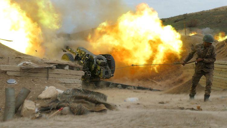 Unsoldat de l'armée de défense du Karabakh tire avec une pièce d'artillerie en direction des positions azerbaïdjanaises, le 4 octobre 2020. (RAZMINFO / ARMENIAN DEFENCE MINISTRY / AFP)
