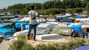 """Un migrants devant le camp de Calais surnommé """"la Jungle"""", le 24 juin 2016. (PHILIPPE HUGUEN / AFP)"""