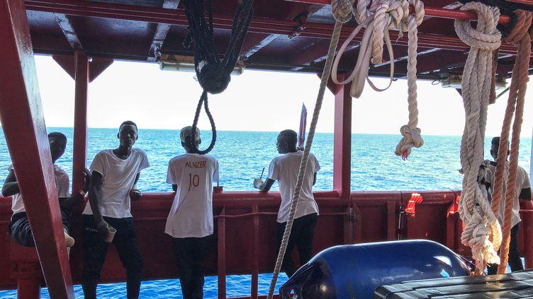 """Des migrants sauvés attendent sur le pont du navire de sauvetage """"Ocean Viking"""", le 20 août 2019. (ANNE CHAON / AFP)"""
