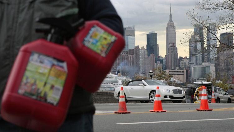 Un homme attend près d'une station-service avec des jerricans pour acheter de l'essence, à Union City, dans le New Jersey, Etat voisin de la ville de New York, le 2 novembre 2012. (EDUARDO MUNOZ / REUTERS)