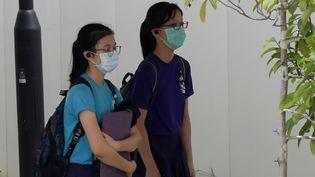 Deux lycéennes portant des masques de protection contre le coronavirus, le 25 mars 2020 à Singapour (ROSLAN RAHMAN / AFP)