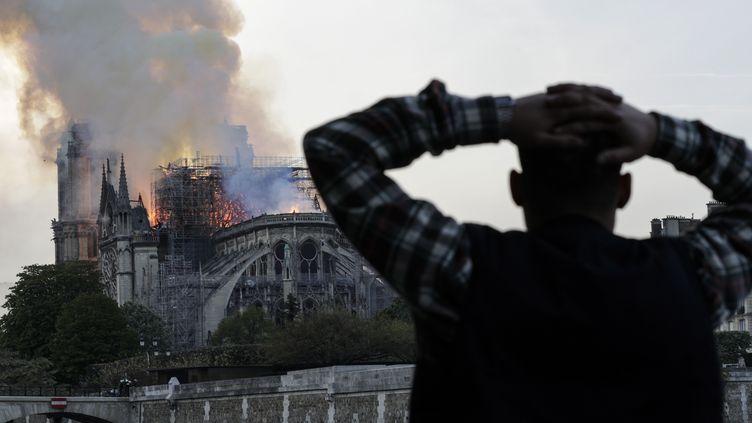 Un homme regarde l'incendie de Notre-Dame, le 15 avril 2019 à Paris. (GEOFFROY VAN DER HASSELT / AFP)