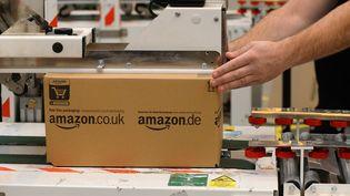 Un employé prépare un colis dans un centre Amazon, à Peterborough (Royaume-Uni), le 28 novembre 2013. (ANDREW YATES / AFP)