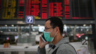 Un passager déambule dans les allées de l'aéroport international de Shanghaï (Chine), le 26 mars 2020. (HECTOR RETAMAL / AFP)