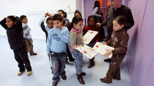 Des enfants discutent avec leur instituteur après une leçon de piano, le 1er février 2008, à l'école Olympe-de-Gouges de Bondy (Seine-Saint-Denis). (PATRICK KOVARIK / AFP)