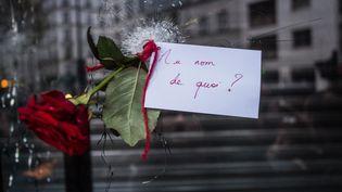 Une rose posée dans un trou formé par une balle, dans une vitre de La Belle Equipe, le 14 novembre 2015, à Paris. (AMINE LANDOULSI / ANADOLU AGENCY / AFP)