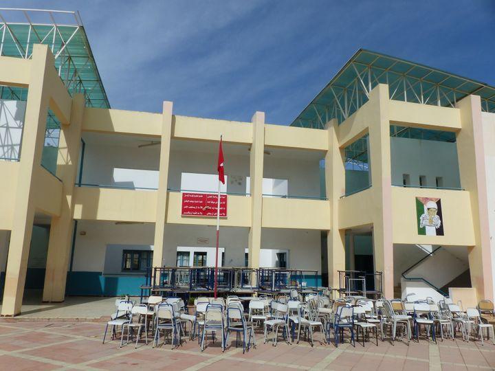 La cour du lycée du quartierElnasr II, le 13 octobre 2019, centre de vote pour le 2e tour de la présidentielle. A droite, la peinture représentant l'enfant palestinien Mohamed Al-Dura, mort en septembre 2000. Au-dessus du podium et du drapeau, une inscription avec certaines des strophes de l'hymne national tunisien. (FTV - Laurent Ribadeau Dumas)